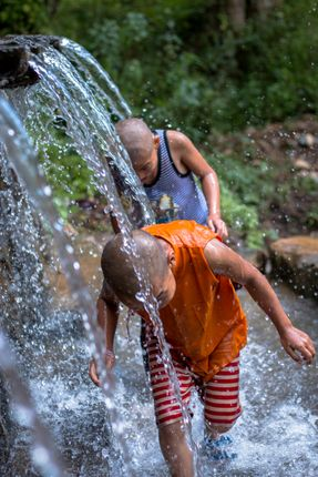 Buddhist,Kids,running,into,the,tap,of,water