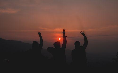 three friends enjoying beautiful sunset