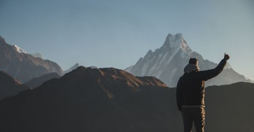 young,man,showing,sign,front,mt,machhapuchhre