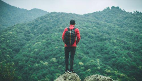 young,boy,standing,facing,hills,bag,back
