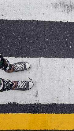minimalist,picture,legs,boy,standing,white,part,zebra,crossing,bright,yellow,line,adding,contrast,image