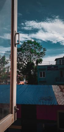 kathmandu,nepal,june,picture,wooden,window,frame,lit,morning,sun,showing,weather,view,house,baneshwor,area